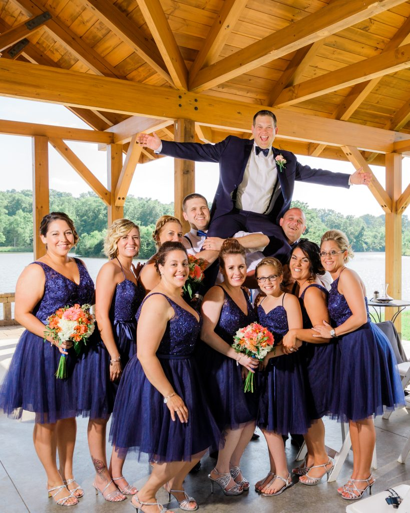 Fun wedding party photo groom on bridesmaids shoulders